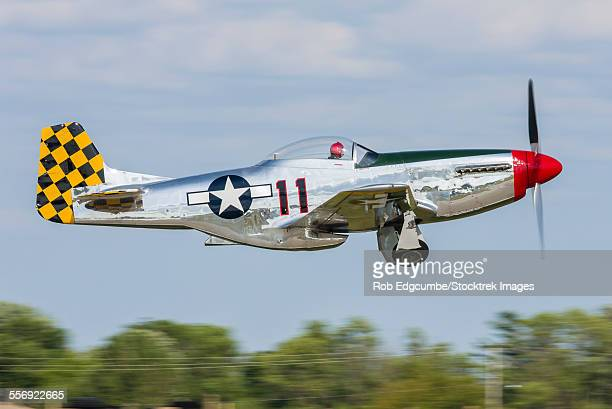 a p-51 mustang takes off from oshkosh, wisconsin, during eaa airventure. - p 51 mustang stock photos and pictures