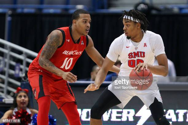 Mustangs forward Ben Moore defended by Cincinnati Bearcats guard Troy Caupain during the second half of the American Athletic Conference championship...