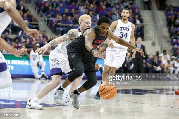 Mustangs guard Jimmy Whitt tries to control the loose ball as TCU Horned Frogs guard Jaylen Fisher defends during the college basketball game between...