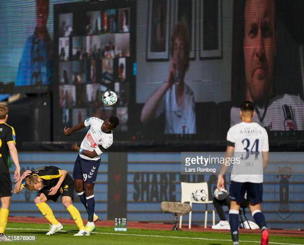 Mustapha Bundu of AGF Aarhus in action in front of the LED screens with fans following the game via zoom during the Danish 3F Superliga match between...