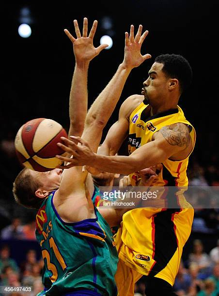Mustapha Farrakhan of the Tigers passes the ball past Jacob Holmes of the Crocodiles during the round 10 NBL match between the Townsville Crocodiles...