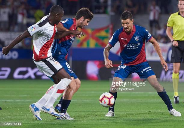 Musto midfielder of SD Huesca competes for the ball with Imbula midfielder of Rayo Vallecano de Madrid during the La Liga game between SD Huesca and...