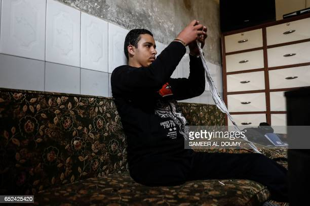 Mute 17yearold Syrian Adnan who lost both legs in 2014 following an airstrike as he was walking towards his father's store from school prepares the...