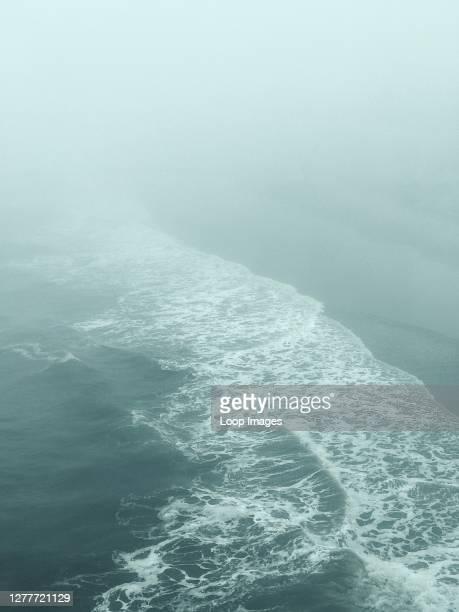 Muted coastline shrouded in mist.