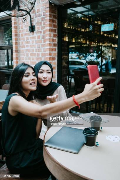 mutilcultural women taking selfie after hacing discussion