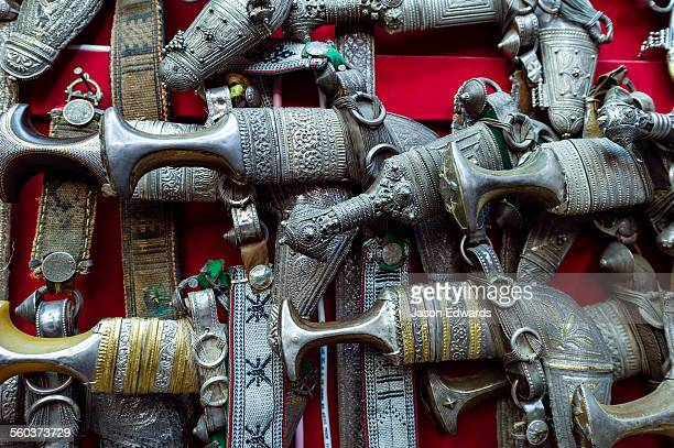 A wall displaying silver khanjar knives for sale in a souq.