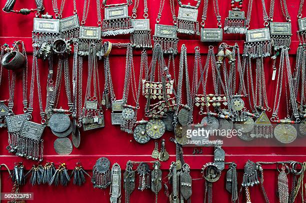 A wall displaying silver necklaces for sale in a souq.