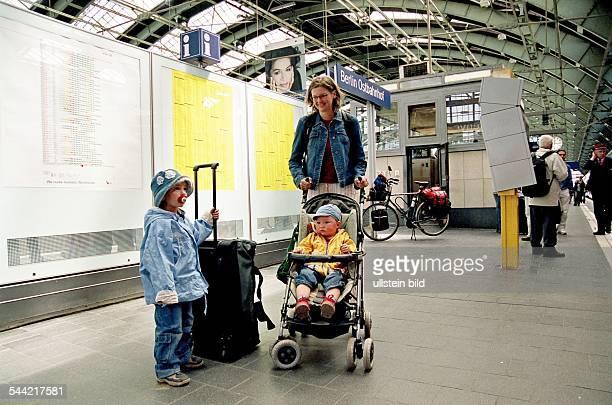 Mutter mit zwei kleinen Kindern wartet auf dem Bahnsteig des Berliner Ostbahnhof vor dem Fahrplan auf den Zug