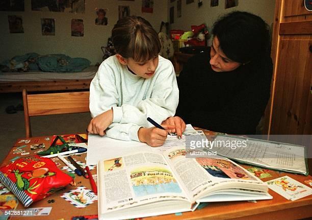 Mutter und Tochter sitzen im Kinderzimmer an einem Schreibtisch bei den Hausaufgaben Der unaufgeräumte Schreibtisch ist mit Stiften und Kleinkram...