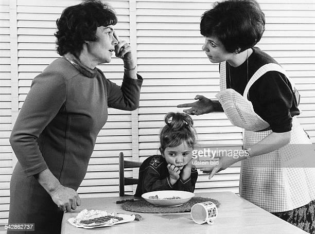 Mutter und Tochter streiten darüber ob ein Kind Schokolade oder das Mittagsbrot essen soll1975