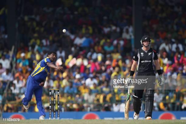 Muttiah Muralitharan of Sri Lanka bowls as Martin Guptill looks on during the 2011 ICC World Cup SemiFinal match between New Zealand and Sri Lanka at...