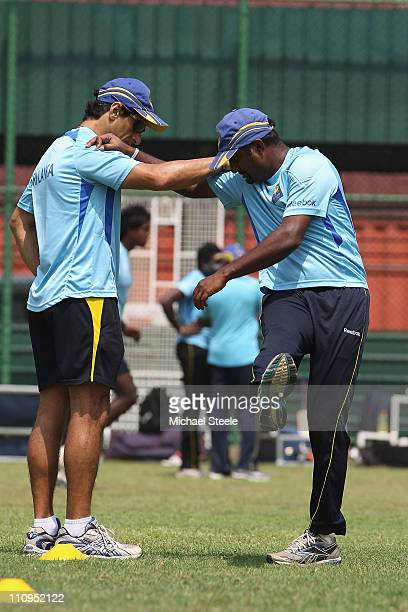 Muttiah Muralitharan of Sri Lanka stretches aided by physio Tommy Simisek during the Sri Lanka nets session at the R. Premadasa Stadium on March 28,...