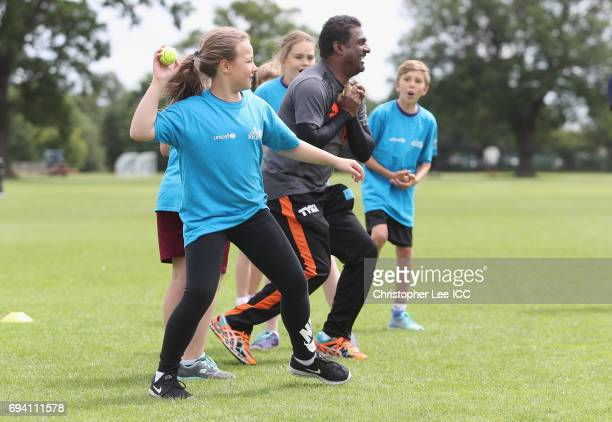 Muttiah Muralitharan plays a cricket game with kids from a local school during the ICC Cricket For Good coaching session with South Africa and...