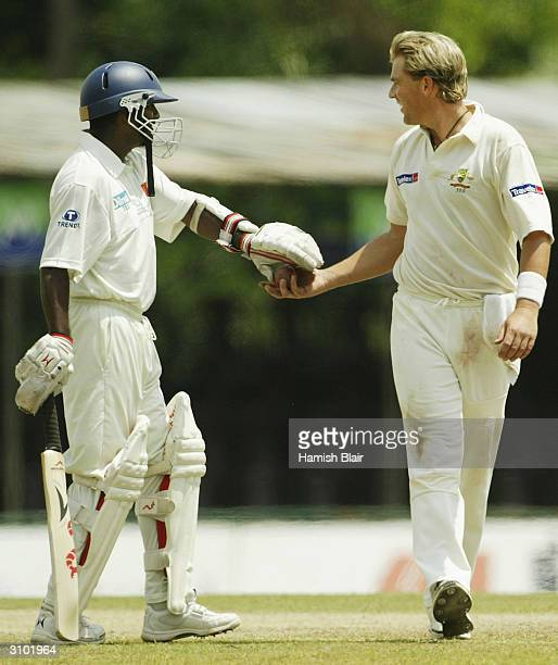 Muttiah Muraltharan of Sri Lanka hands the ball to Shane Warne of Australia during day two of the Second Test between Australia and Sri Lanka played...