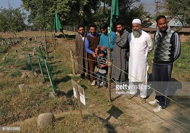 Muzaffar Wani father of rebel commander Burhan Wani stands with neighbours in the graveyard where his son and rebel commander Burhan Wani is buried...