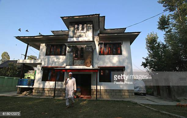 Muzaffar Wani father of rebel commander Burhan Wani walks in the lawn of his residence in Shareef Abad village in south Kashmirs Tral some 40...