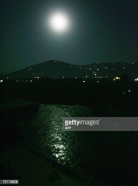 An early morning full moon scene of the devastated city of Muzaffarabad the capital of Pakistani administered Kashmir 08 October 2006 on the day of...