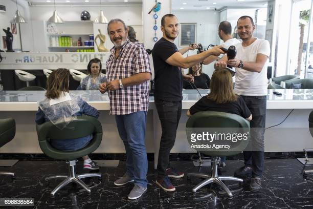 Muzaffer Tunc a hairdresser poses for a photo with his 36yearold son Timur and 33yearold son Tolga who had chosen the same field of profession with...