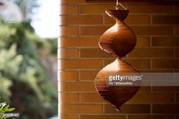 móvil de madera iluminado por el sol con una pared de ladrillo y vegetación de fondo