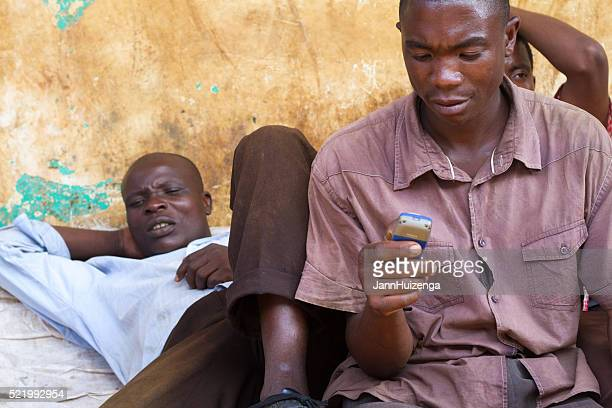 mwanza, tanzania: men relaxing, one with cell phone - black alley stock photos and pictures
