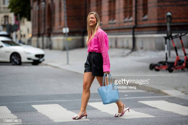 My Andrén wearing pink blouse black shorts blue bag heels seen during Stockholm Fashion Week Digital Edition 2020 on August 25 2020 in Stockholm...