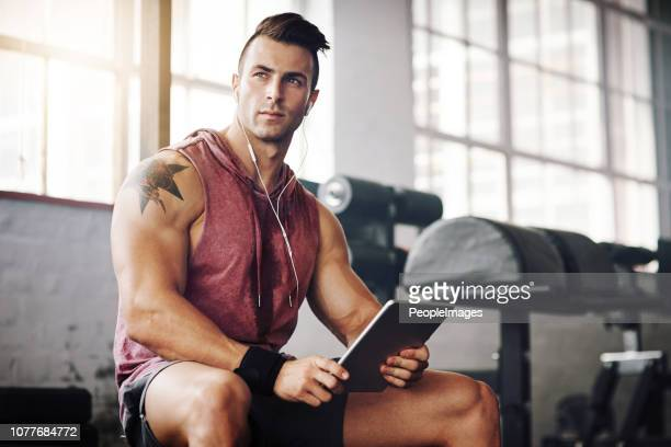 my device is used for music and workout apps - handsome bodybuilders stock pictures, royalty-free photos & images