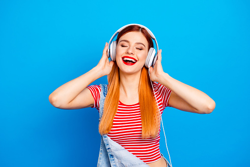My favorite track! Close up photo portrait of positive optimistic with beaming toothy smile long hairstyle wearing white headset girl isolated bright vivid background 1041863124