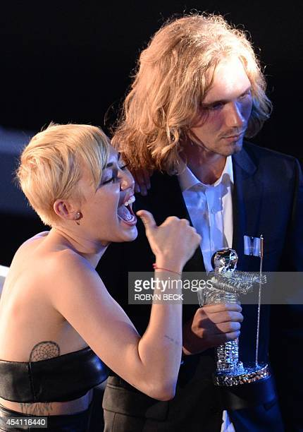 My Friend's Place representative Jesse accepts Video of the Year with singer Miley Cyrus for 'Wrecking Ball' on stage at the MTV Video Music Awards...