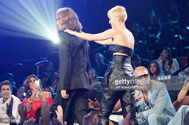My Friend's Place representative Jesse Helt and singer Miley Cyrus speak onstage during the 2014 MTV Video Music Awards at The Forum on August 24...