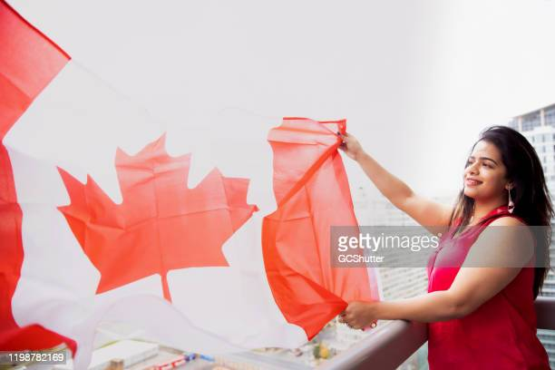 my love for canada! - girl flying canadian flag to celebrate the canada day on 1st july - canada day stock pictures, royalty-free photos & images