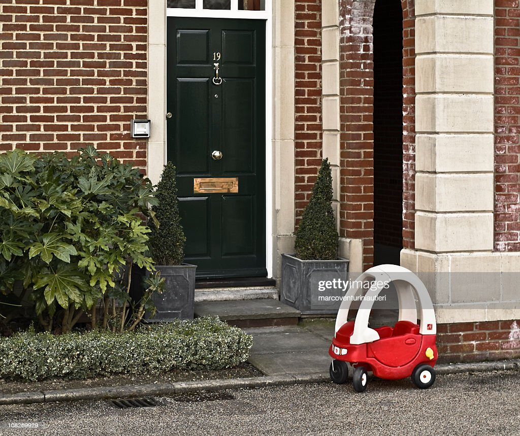 My other car's a limo!  Children's car parked house entrance : Stock Photo