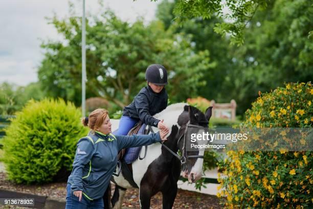 mijn trainer helpt mij slagen - paardrijden stockfoto's en -beelden