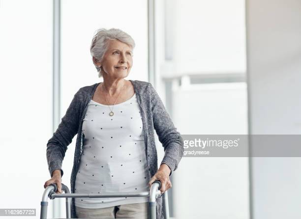 my walker helps me to get around - osteoporosis stock pictures, royalty-free photos & images