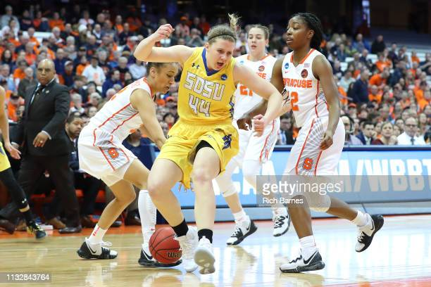Myah Selland of the South Dakota State Jackrabbits loses control of the ball between Miranda Drummond and Kiara Lewis of the Syracuse Orange during...
