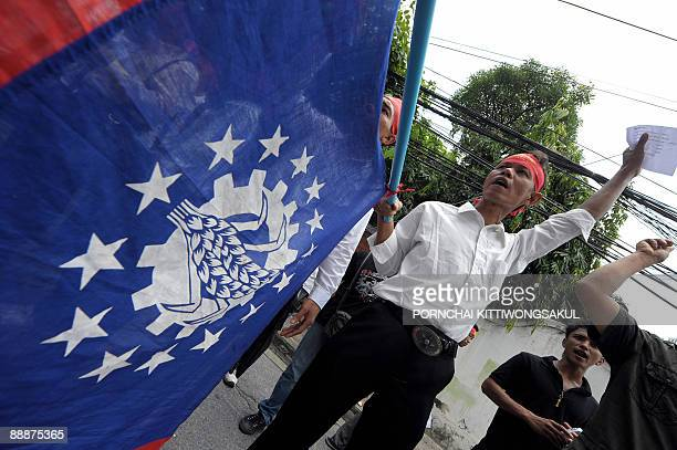 Myanmar activists shout slogans while wave national flags during a demonstration at the Myanmar embassy in Bangkok on July 7, 2009. The activists...