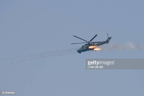 A Myanmar Air Force Mi35 attack helicopter launches a salvo of rockets during the 'Sin Phyu Shin' joint military exercises near Pathein city in the...