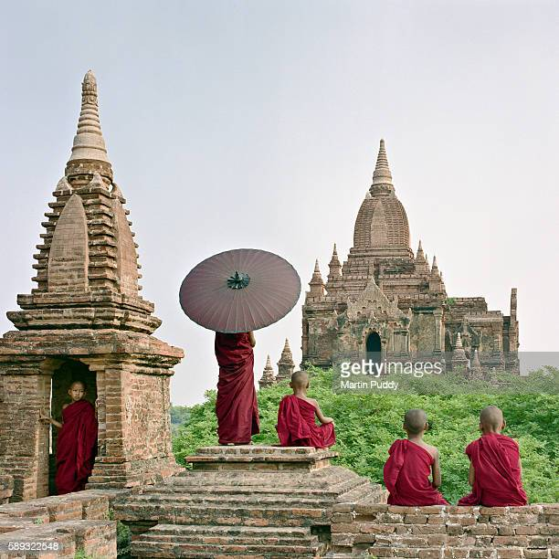 myanmar, bagan, buddhist monks standing on temple top - myanmar stock pictures, royalty-free photos & images