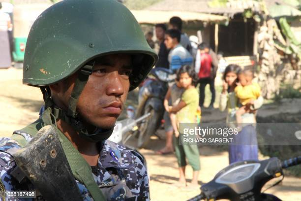 A Myanmar border guard policeman stand near a group of Rohingya Muslims in front of their homes in a village are seen during a governmentorganized...