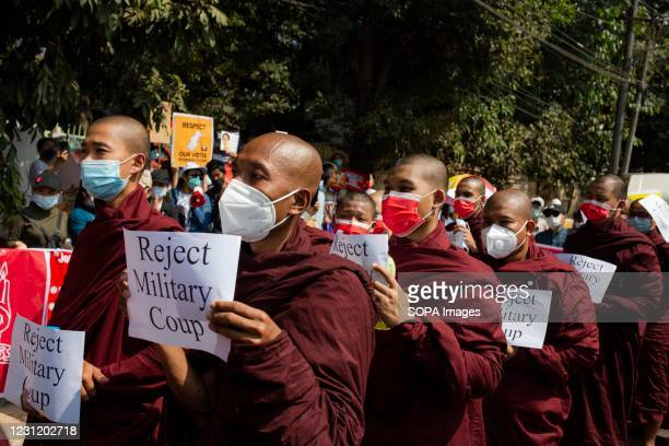 Myanmar Buddhist monks march through the Streets while holding placards during the demonstration. Thousands of people took to the streets of Yangon...