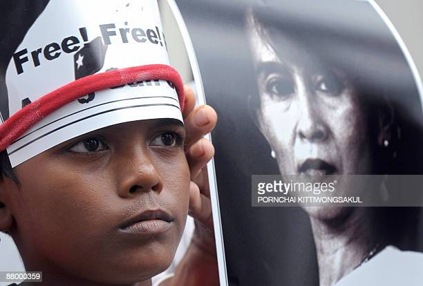 A Myanmar child stands next to a portrait of Myanmar democracy icon Aung San Suu Kyi during a protest at the Myanmar embassy in Bangkok on May 27...