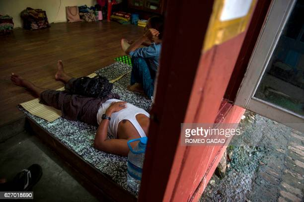 A Myanmar couple living with HIV virus after the husband was infected by a sex worker rests at the National League for Democracy HIV/AIDS Center with...