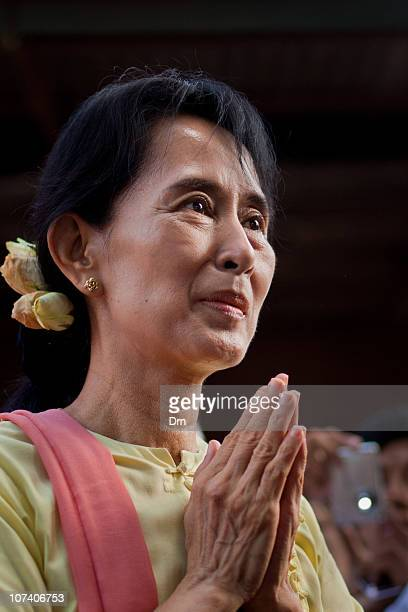 Myanmar democracy icon Aung San Suu Kyi clasps her hands as she hands out donations to Buddhist nuns and monks at the National League for Democracy...