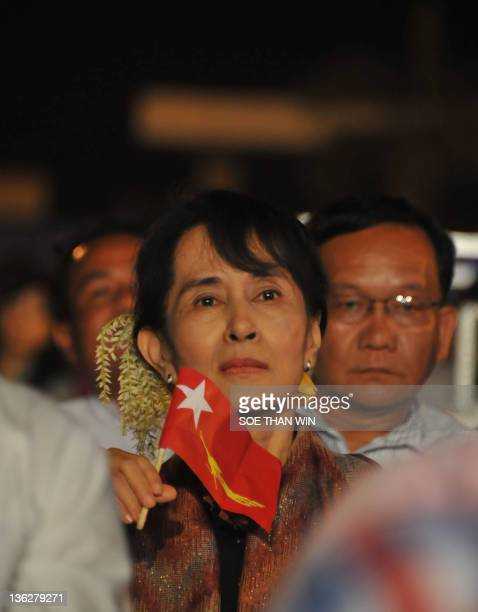 Myanmar democracy icon Aung San Suu Kyi holds the new National League for Democracy party's flag during a music concert funfair in Yangon on December...