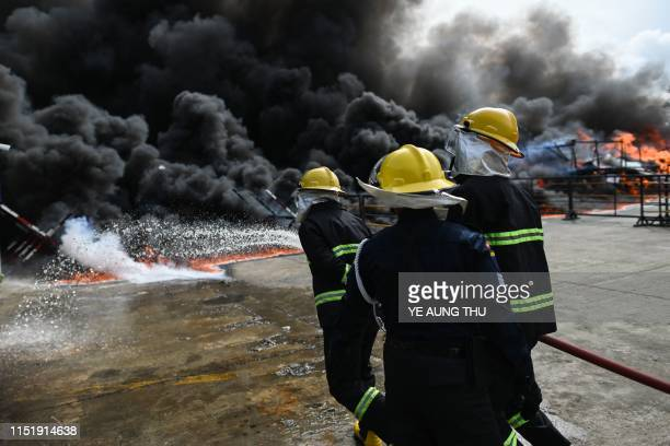 Myanmar firefighters control fire on a pile of burning drugs during a destruction ceremony to mark the UN's International Day against Drug Abuse and...