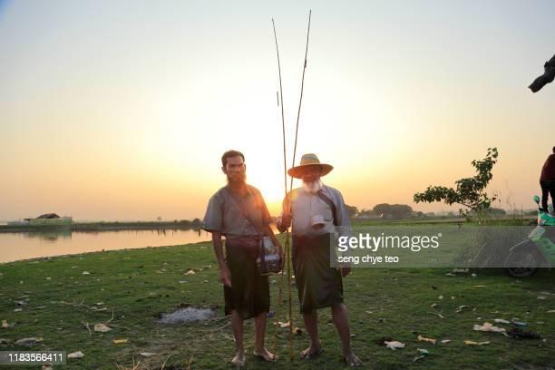 myanmar fisherman walking across u bein bridge, mandalay, myanmar - teak wood material stock pictures, royalty-free photos & images
