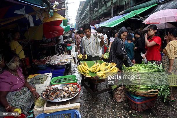A Myanmar fruits vendor makes his way through a street market in Lanmadaw township downtown Yangon on June 15 2010 Myanmar faces a tough task to...