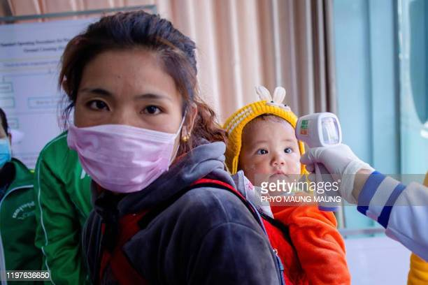 A Myanmar health officer checks the temperature of a child entering the MyanmarChina border crossing checkpoint in Muse Shan State on January 31 2020...