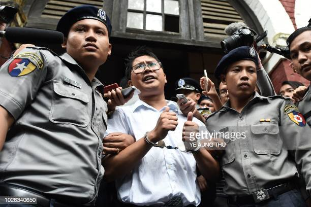 TOPSHOT Myanmar journalist Wa Lone is escorted by police after being sentenced by a court to jail in Yangon on September 3 2018 Two Reuters...