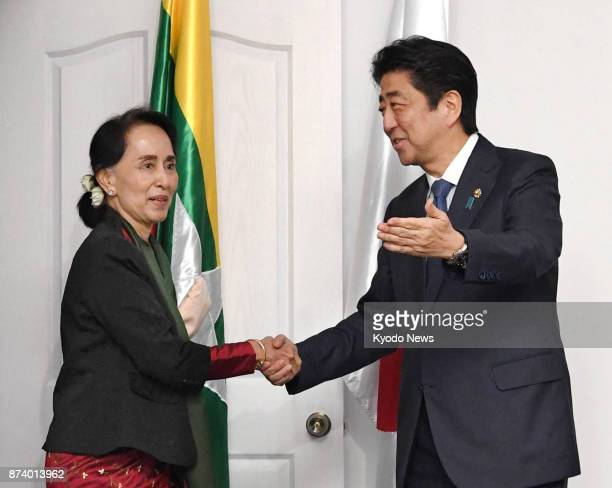 Myanmar leader Aung San Suu Kyi shakes hands with Japanese Prime Minister Shinzo Abe ahead of their talks in Manila on Nov 14 2017 ==Kyodo