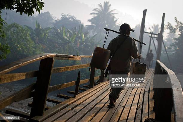 A Myanmar man carries water over a bridge inside the Mae La refugee camp on the ThaiMyanmar border around 80km from Mae Sot northwest Thailand on...